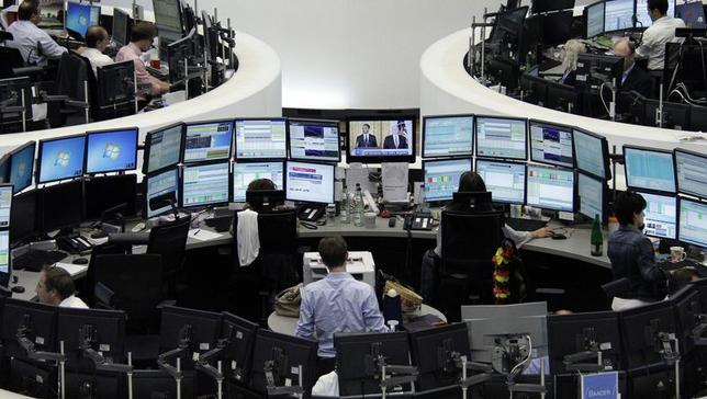 Traders are pictured at their desks in front of the DAX board at the Frankfurt stock exchange August 1, 2014. REUTERS/Pawel Kopczynski/Remote