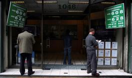 Unas personas revisan cotizaciones de dinero en una casa de cambios en el centro de Santiago, oct 13 2008. Los operadores de monedas latinoamericanas buscarán precisiones sobre el momento en el que la Reserva Federal estadounidense podría subir las tasas en tres eventos de esta semana: el reporte de la inflación de julio, las minutas de la Fed y una reunión de economistas en Jackson Hole. REUTERS/Ivan Alvarado