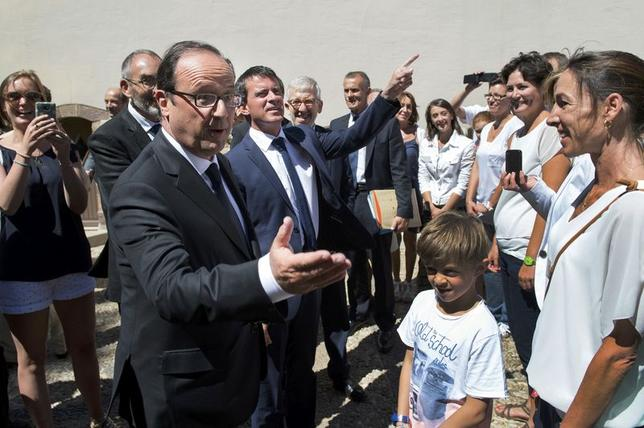 French President Francois Hollande (L) and French Prime Minister Manuel Valls are greeted by well-wishers as they arrive at the Fort de Bregancon for a working lunch in Bormes-les-Mimosas, southeastern France, August 15, 2014. REUTERS/Bertrand Langlois/Pool