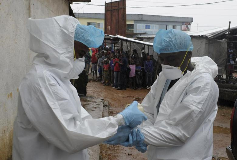 Health workers wear protective clothing before carrying an abandoned dead body presenting with Ebola symptoms at Duwala market in Monrovia August 17, 2014.  REUTERS/2Tango
