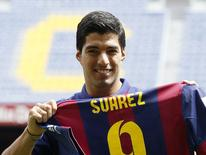 FC Barcelona's Luis Suarez holds up his jersey during his presentation at the Nou Camp stadium in Barcelona August 19, 2014.  REUTERS/Gustau Nacarino
