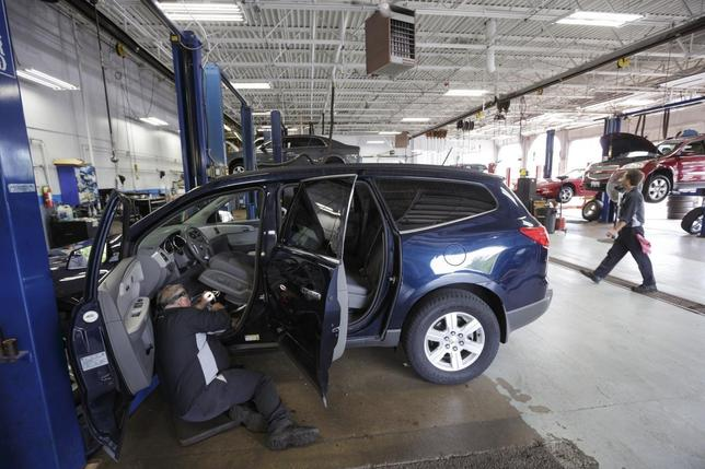 Technician Bob Poe works on wiring under the drivers seat of a Chevy Traverse because of a recall at Raymond Chevrolet in Antioch, Illinois, July 17, 2014.   REUTERS/John Gress