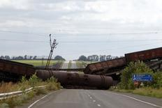 Вагоны на ращрушенном железнодорожном мосту близ деревни Новобахмутовка 19 августа 2014 года.  Военный конфликт с пророссийскими сепаратистами на востоке Украины истощает экономику страны, заставляя тратить миллиарды на восстановление разрушенной инфраструктуры и препятствуя быстрому проведению необходимых реформ, сказал премьер-министр Арсений Яценюк. REUTERS/Valentyn Ogirenko