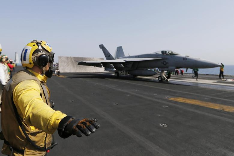 Flight deck crew member confirms the deck is all clear before a F/A-18C Hornet of Strike Fighter Squadron (VFA-87) take offs the aircraft carrier USS George H.W. Bush (CVN 77), in the Gulf August 12, 2014.  REUTERS/Hamad I Mohammed