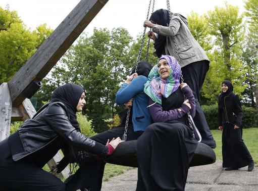 Yasmin (L), 16, pushes Hana (C), 16, on a swing after finishing a GCSE exam near their school in Hackney, east London June 6, 2013.  REUTERS/Olivia Harris