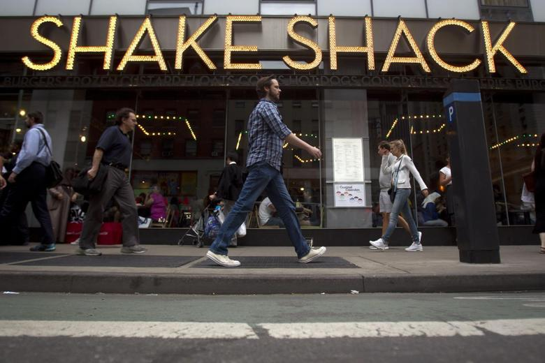 People walk past a Shake Shack restaurant in the Manhattan borough of New York August 15, 2014. REUTERS/Carlo Allegri