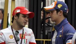 Ferrari's Formula One driver Felipe Massa (L) of Brazil chats with his compatriot, Nelson Piquet Junior, at the pit-lane in Sao Paulo October 18, 2007.   REUTERS/Paulo Whitaker
