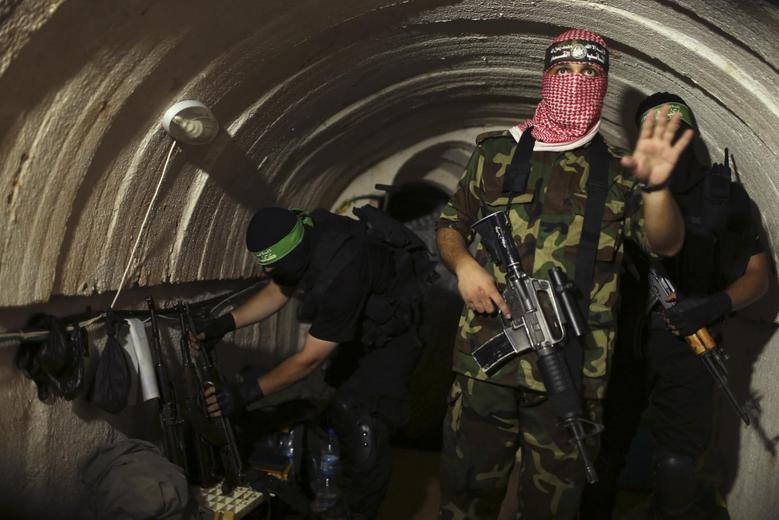 A Palestinian fighter from the Izz el-Deen al-Qassam Brigades, the armed wing of the Hamas movement, gestures inside an underground tunnel in Gaza August 18, 2014.  REUTERS/Mohammed Salem