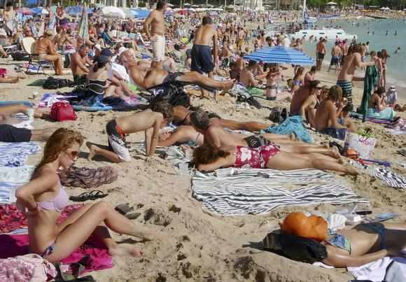 Tourists enjoy the sun on New Year's Day on Waikiki Beach in Honolulu, Hawaii in this file photo taken January 1, 2010. REUTERS/Larry Downing