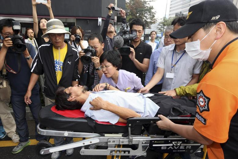 Kim Young-oh, 47, who lost his 16-year-old daughter in the ferry disaster, is wheeled to an ambulance on a stretcher after 40 days of fasting in Seoul August 22, 2014.   REUTERS/Han Jae-ho/News1