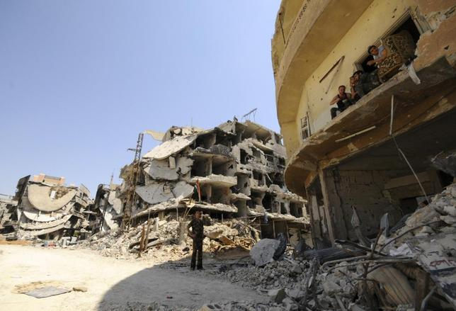 A Syrian army soldier loyal to Syria's President Bashar al-Assad chats with fellow fighters sitting on a balcony of a damaged building in Mleiha, which lies on the edge of the eastern Ghouta region near Damascus airport, after taking control of the area from rebel fighters August 15, 2014.  REUTERS/Omar Sanadiki