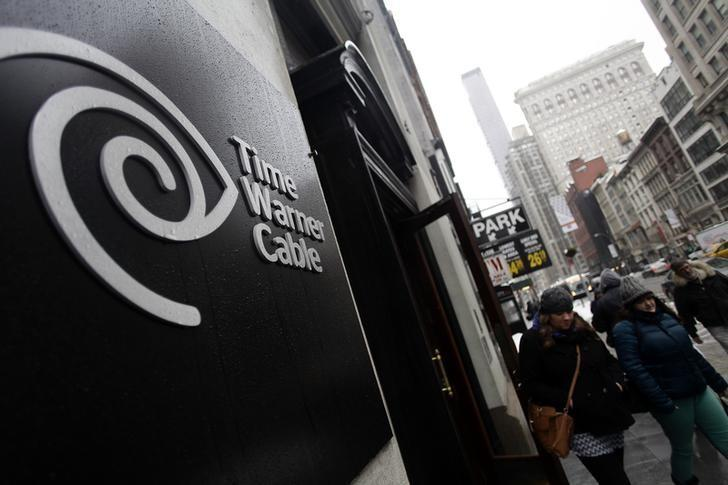 Pedestrians walk past the Time Warner Cable headquarters in New York February 13, 2014. REUTERS/Joshua Lott