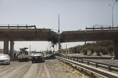 A general view of the damage of the 27th Bridge is seen along a road linking Tripoli and the western Libyan cities, near a former Libyan Army camp known as Camp 27 following clashes between rival militias in the 27 district, west of Tripoli, August 22,2014. REUTERS/Stringer
