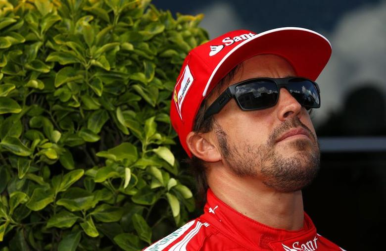 Ferrari Formula One driver Fernando Alonso of Spain looks up during his walk in the paddock ahead of the weekend's Belgian Grand Prix in Spa-Francorchamps August 21, 2014. REUTERS/Yves Herman