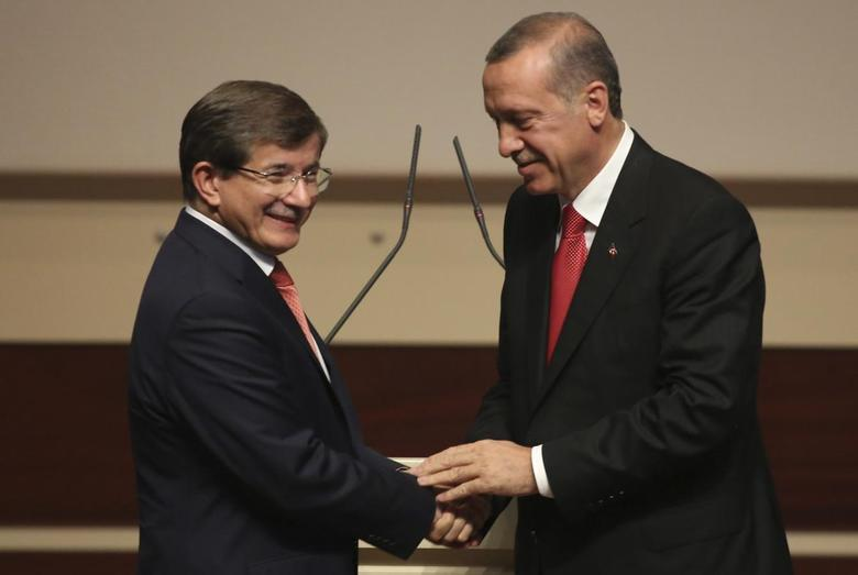 Turkey's Prime Minister Tayyip Erdogan (R) shakes hands with Foreign Minister Ahmet Davutoglu during a meeting at the AK Party headquarters in Ankara August 21, 2014.  REUTERS/Stringer