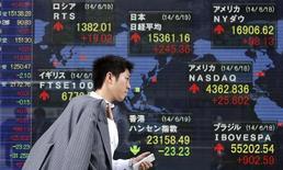 Прохожий у брокерской конторы в Токио 19 июня 2014 года. Азиатские фондовые рынки, кроме Китая, выросли в понедельник за счет отдельных компаний и отраслей. REUTERS/Yuya Shino