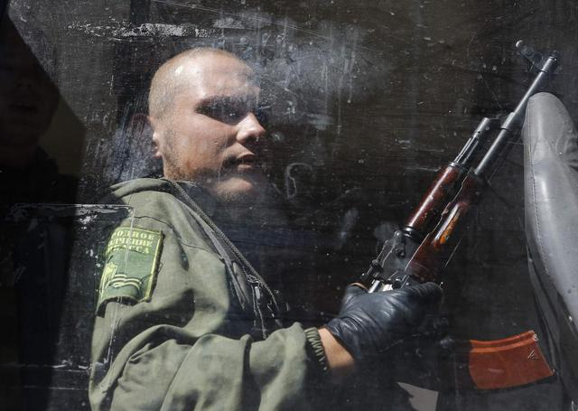 An armed pro-Russian separatist sits in a bus after a rally in Donetsk August 24, 2014. REUTERS/Maxim Shemetov