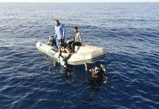 Membros da guarda costeira da Líbia recuperam corpo de homem que morreu afogado na costa de Trípoli. 23/08/2014 REUTERS/Aimen Elsahli