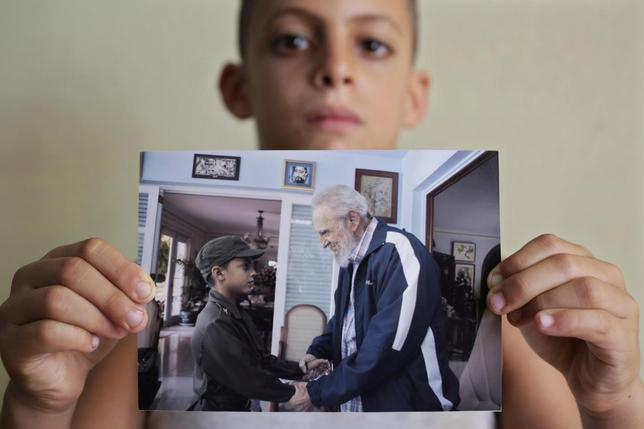 Eight-year-old Marlon Mendez, who claims to be an admirer of Cuba's former president Fidel Castro, holds a picture of him and Castro, in San Antonio de los Banos, outside Havana City August 23, 2014. REUTERS/Enrique De La Osa