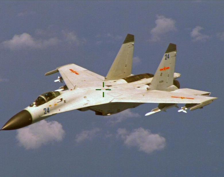 A Chinese J-11 fighter jet is seen flying near a U.S. Navy P-8 Poseidon about 215 km (135 miles) east of China's Hainan Island in this U.S. Department of Defense handout photo taken August 19, 2014. REUTERS/U.S. Navy/Handout