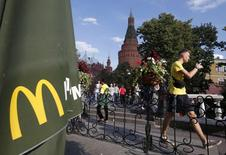 A man walks past a closed McDonald's restaurant, one of four temporarily closed by the state food safety watchdog, with the Kremlin seen in the foreground, in Moscow, August 21, 2014. REUTERS/Maxim Zmeyev