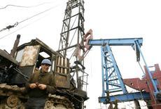 Рабочий на нефтяном месторождении в Баку 17 марта 2009 года. Цены на нефть Brent приближаются к $103 за баррель, поднимаясь с 14-месячного минимума, но избыток предложения на мировом рынке сдерживает рост. REUTERS/David Mdzinarishvili