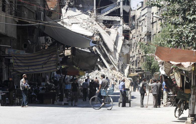 Residents walk past damaged buildings as they shop in the Damascus suburb of Harasta August 24, 2014. Picture taken August 24, 2014. REUTERS/Badra Mamet