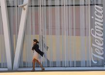 El consejo de administración de Telefónica tiene previsto estudiar este miércoles una mejora de su oferta por GVT, el operador de banda ancha brasileño perteneciente a Vivendi, dijo a Reuters una fuente familiarizada con la situación, aunque desmintió informaciones de prensa de que Telefónica llegaría a ofrecer hasta 8.000 millones de euros. En la imagen, una mujer pasa junto a un edificio de Telefónica en Barcelona, el 31 de julio de 2014. REUTERS/Albert Gea