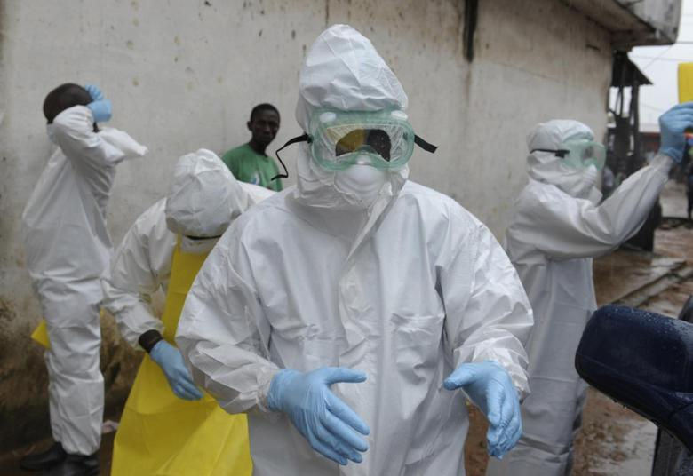 Health workers wearing protective clothing prepare to carry an abandoned dead body presenting with Ebola symptoms at Duwala market in Monrovia August 17, 2014. REUTERS/2Tango