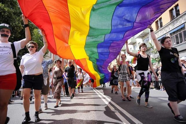 Participants carrying a rainbow flag attend the annual gay pride parade in Stockholm August 2, 2014. REUTERS/Annika Af Klercker/TT News Agency