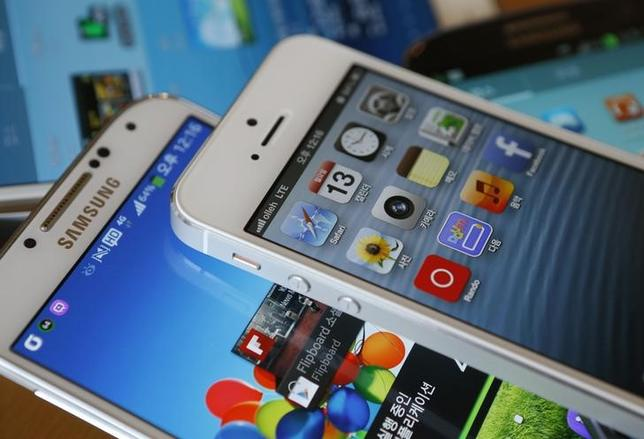 Apple's iPhone 5 (top) and Samsung Electronics' Galaxy S4 are seen in this picture illustration taken in Seoul May 13, 2013.  REUTERS/Kim Hong-Ji