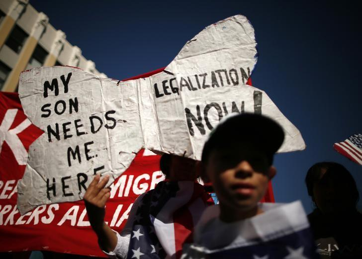 An undocumented immigrant who said she has lived in the U.S. for 26 years, holds a sign as she marches with her son to demand immigration reform in Hollywood, Los Angeles, California, October 5, 2013. REUTERS/Lucy Nicholson