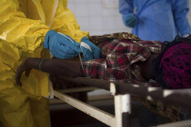 Medical staff take a blood sample from a suspected Ebola patient at the government hospital in Kenema, July 10, 2014. REUTERS/Tommy Trenchard