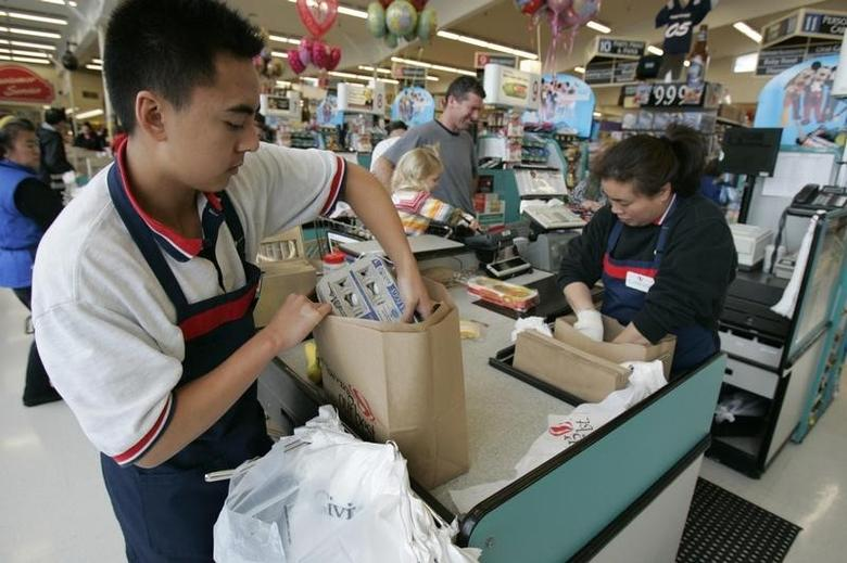 Grocery store employees fill bags in San Francisco, California, January 26, 2005.  REUTERS/Kimberly White