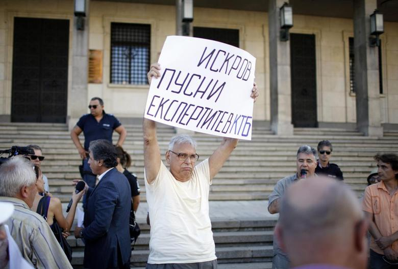A depositor at Bulgaria's Corporate Commercial Bank (Corpbank) holds a sign during a demonstration demanding access to their accounts in Corpbank, in front of the Bulgarian National Bank in Sofia August 19, 2014.  REUTERS/Pierre Marsaut