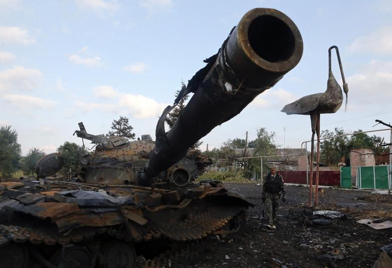 A Pro-Russian separatist walks past a destroyed tank at Savur-Mohyla, a hill east of the city of Donetsk, August 28, 2014. REUTERS/Maxim Shemetov