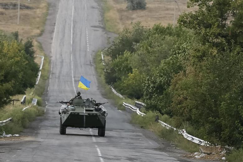 Ukrainian servicemen ride in an armoured vehicle near Debaltseve, Donetsk region, August 29, 2014. REUTERS/Gleb Garanich