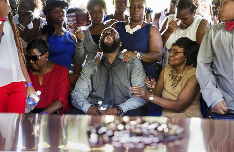 Michael Brown Sr, yells out as his son's casket is lowered into the ground at St. Peter's Cemetery in St. Louis, Missouri, August 25, 2014.  REUTERS/Richard Perry/Pool