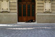 Un vagabundo durmierno en la entrada de la Bolsa de Comercio de Santiago, ago 26 2014. La tasa de desempleo en Chile se mantuvo sorpresivamente estable en 6,5 por ciento en el trimestre móvil mayo-julio, pese a la mayor desaceleración de la economía doméstica y los negativos efectos estacionales, mostraron el viernes datos del Gobierno. REUTERS/Ivan Alvarado