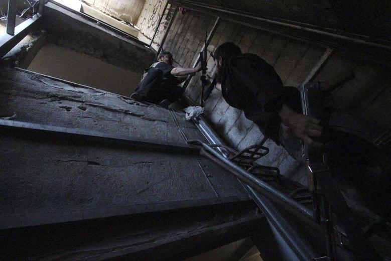 A rebel fighter hands a weapon to his fellow fighter as they move inside a building on the frontline in the Damascus suburb of Harasta August 24, 2014. REUTERS/Badra Mamet