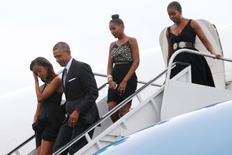 U.S. President Barack Obama and first lady Michelle Obama (R), with their daughters Malia (L) and Sasha (2nd R) arrive aboard Air Force One at Westchester County Airport in White Plains, New York August 30, 2014. REUTERS/Jonathan Ernst