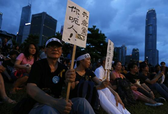 A pro-democracy protester carries a placard which reads 'Communist Party, you lie!' as he sits with other protesters during a campaign to kick off the Occupy Central civil disobedience event in front of the financial Central district in Hong Kong August 31, 2014. REUTERS-Bobby Yip