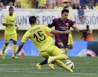Barcelona's Lionel Messi (R) is challenged by Villareal's Victor Ruiz during their Spanish first division soccer match at the Madrigal stadium in Villarreal August 31, 2014. REUTERS/Heino Kalis