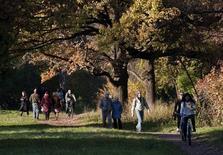 Люди гуляют в парке в Москве 10 октября 2010 года. К концу рабочей недели погода в Москве улучшится - в российской столице потеплеет и будет больше солнца, ожидают синоптики. REUTERS/Nikolai Korchekov