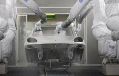 Роботы красят автомобиль Porsche Macan на заводе в Лейпциге 5 февраля 2014 года. Рост производственного сектора еврозоны замедлился в августе немного сильнее, чем думали первоначально, так как число новых заказов снизилось, а фабрики пострадали на фоне растущего напряжения на Украине. REUTERS/Tobias Schwarz