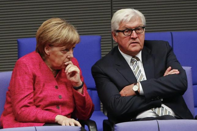 German Chancellor Angela Merkel (L) and Foreign Minister Frank-Walter Steinmeier talk during a debate about the situation in Iraq in the lower house of parliament, the Bundestag, in Berlin, September 1, 2014.  REUTERS/Thomas Peter