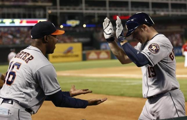 Apr 12, 2014; Arlington, TX, USA; Houston Astros left fielder Robbie Grossman (19) is congratulated by manager Bo Porter (16) after homering during the fourth inning of a baseball game against the Texas Rangers at Globe Life Park in Arlington. Mandatory Credit: Jim Cowsert-USA TODAY Sports