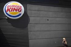A man talks on his phone underneath a Burger King logo outside the restaurant in the Brooklyn borough of New York August 25, 2014.  REUTERS/Carlo Allegri