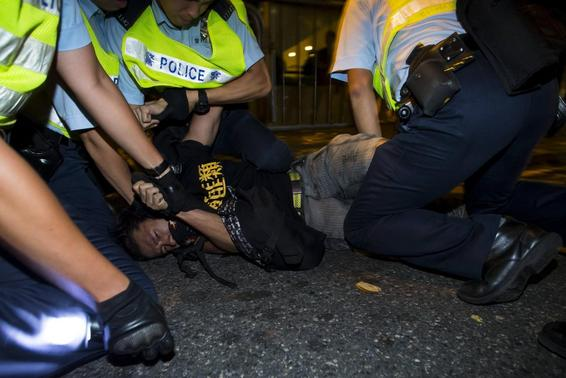 A pro-democracy activist is detained by the police during a confrontation outside the hotel where China's National People's Congress (NPC) Standing Committee Deputy General Secretary Li Fei is staying, in Hong Kong September 1, 2014.  REUTERS/Tyrone Siu