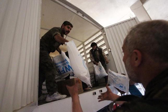 People unpack humanitarian aid inside a warehouse in Ghouta, eastern Damascus May 24, 2014. REUTERS/Badra Mamet
